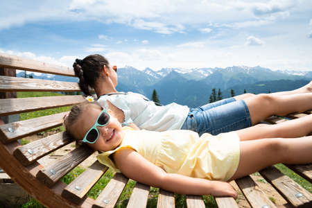 Little Girl And Her Mother Relaxing In Sun Lounger In Mountains