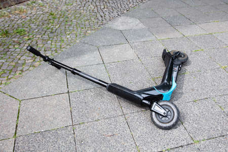 Overhead View Of Electric Scooter Lying On Concrete Street After Accident