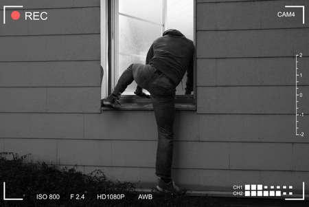 Vista trasera de un ladrón entrando en una casa a través de una ventana abierta Foto de archivo