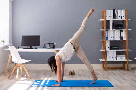 Happy Young Businesswoman Doing Stretching Exercise At Workplace
