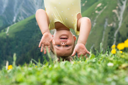 Little Girl Hanging Upside Down In Mountains Stockfoto