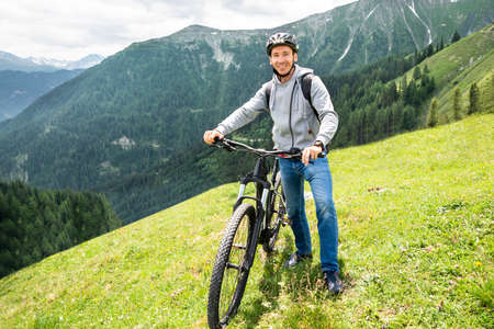 Main On Mountain With His Bike In Alps Stockfoto