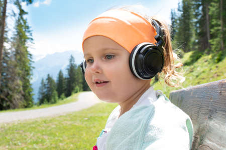 Little Girl In Headphone Listening Music In Mountains Stockfoto