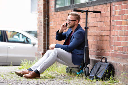 A Handsome Businessman Sitting On Electric Scooter Using Cellphone Near Brick wall Stockfoto