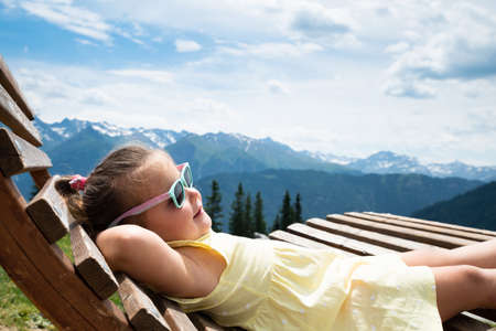 Little Girl Relaxing In Sun Lounger In Mountains