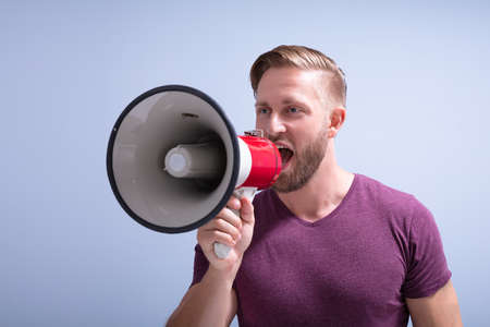 Close-up Of A Beard Man Shouting Through A Megaphone Against Gray Background Stockfoto
