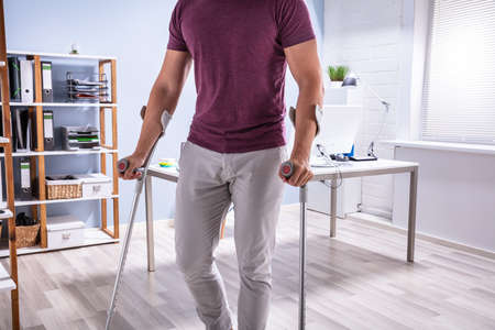 Handicapped Businessman Walking On Hardwood Floor With Crutches At Workplace