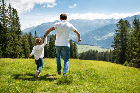 Father And Daughter Holding Hands Running On Field In Mountains