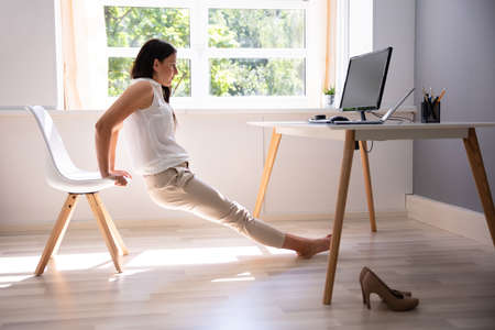 Side View Of A Young Woman Doing Stretching Exercise In Office