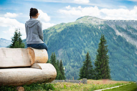 Woman Sitting On Bench Enjoying Panoramic Mountain View
