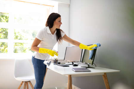 Young Woman Cleaning Computer With Blue Napkin In Office