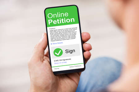 Man Looking At Online Petition Form On Smartphone Stockfoto