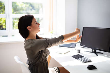 Rear View Of Young Businesswoman Stretching Her Arms In Office Stockfoto