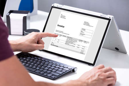 Close-up Of Businessmans Hands Working On Invoice On Laptop At Office