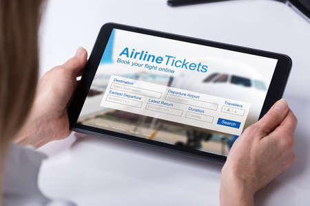 Woman Booking Online Air Tickets By Using Tablet At Home