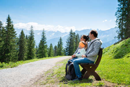 Family Sitting On Bench On Hiking Trail Resting In Mountains Stockfoto