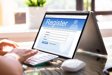 Woman Filing Online Registration Form On Laptop