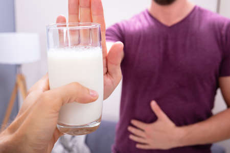 Close-up Of A Man Rejecting Glass Of Milk Offered By Person At Home
