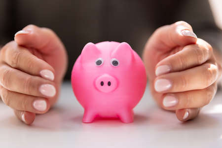 Close-up Of A Human Hand Protecting Pink Piggy Bank On White Desk Stockfoto