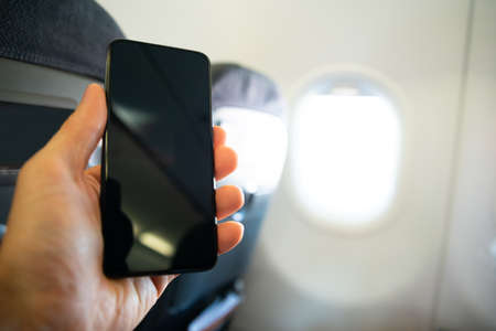 Close-up Of Persons Hand Using Mobile Phone With Blank Screen In Airplane