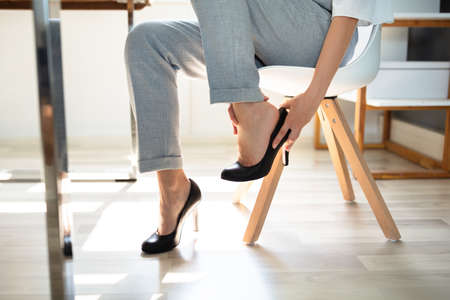 Young Businesswoman Suffering From Leg Pain Because Of Uncomfortable Shoes In Office