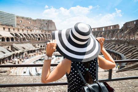 Rear View Of Female Tourist Standing Inside Colosseum In Rome Looking At Arena Stockfoto