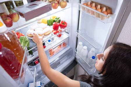 An Elevated View Of A Young Woman Taking Food To Eat From Refrigerator Stockfoto