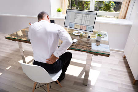 Businessman Suffering From Back Pain At Office Desk