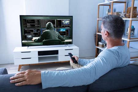 Vista trasera del hombre viendo la televisión en casa