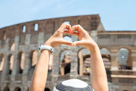 Woman Making Heart Shape In Front Of Colosseum, Italy