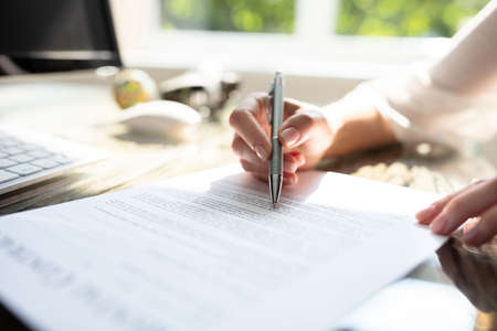 Close-up Of Businesswomans Hand Signing Contract With Pen Over Desk In Office Stockfoto