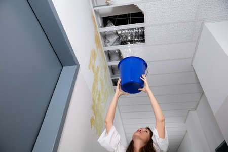 Worried Woman Holding A Blue Bucket Under The Leak Ceiling In Corridor Stockfoto