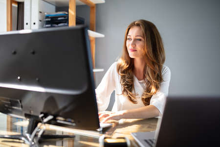 Smiling Young Businesswoman Working At Workplace In Front Of Computer Stockfoto