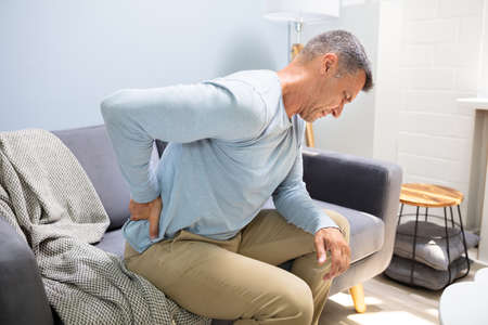 Man On Sofa Suffering From Backpain At Home