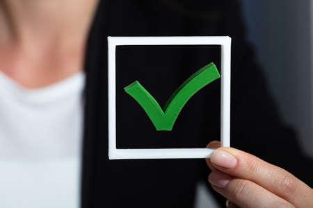 Primo piano della mano di un uomo d'affari che tiene l'icona del segno di spunta verde