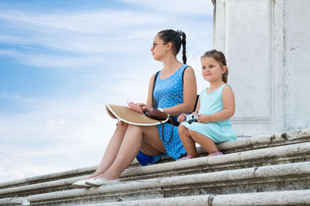 Young Mother With Her Daughter Sitting On Stairs In Front Of Historical Building