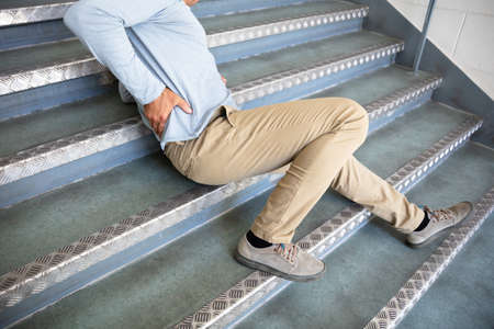 Mature Man Lying On Staircase After Slip And Fall Accident Banque d'images