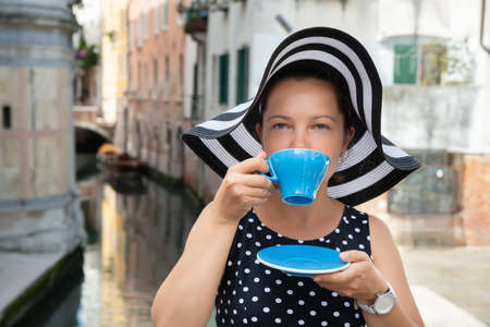 Portrait Of Beautiful Young Woman Wearing Hat Drinking Coffee From Blue Cup At Venice