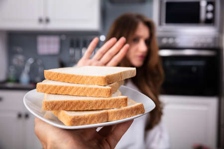 Young Woman Refusing Bread Slice On Plate At Home