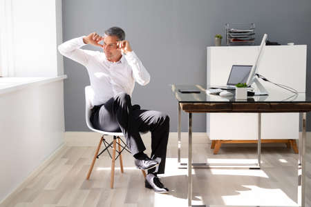 Happy Businessman Doing Stretching Exercise In Office