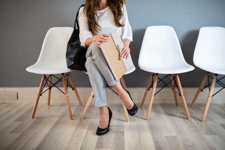 Young Businesswoman Holding Folder alors qu'il était assis sur une chaise en attente d'un entretien d'embauche