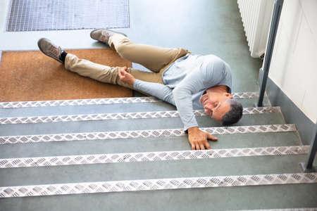 Hombre maduro, acostado en la escalera después de un accidente de resbalón y caída Foto de archivo