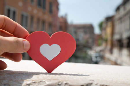 Person Holding Red And White Heart Shape In Sunlight On Railing At Venice