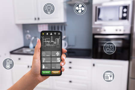 Close-up Of A Persons Hand Using Smart Home System Application On Mobilephone