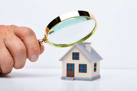Close-up Of Person Hand Holding Magnifying Glass Over A Miniature House On The Table