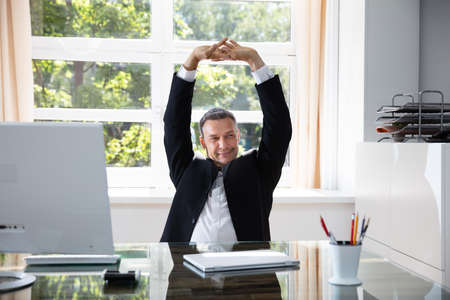Happy Businessman Stretching His Arms In Office