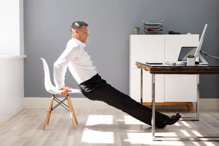 Side View Of A Young Businessman Doing Triceps Dips In Office