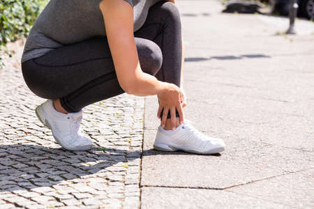 Close-up Of Female Jogger Suffering From Ankle Injury On Street Stock Photo