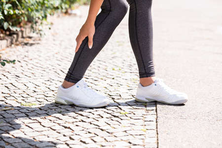 Close-up Of A Female Runner Suffering From Pain In Calf Muscle Stock Photo