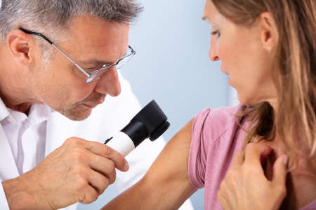 Close-up Of A Doctor Checking Skin Of Female Patient With Dermatoscope